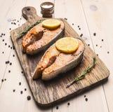 在一个切板的开胃油煎的鲑鱼排有柠檬、迷迭香和胡椒未磨过的关闭的 库存照片