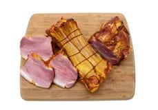 在一个切板的开胃熏制的猪肉在白色背景 免版税库存图片