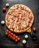 在一个切板的新近地煮熟的烤肉比萨 免版税图库摄影