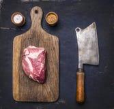 在一个切板的新鲜的未加工的猪肉牛排有葡萄酒在黑暗的木背景的切肉刀的用胡椒,盐 免版税库存照片