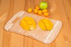 在一个切板的新鲜的芒果用新鲜的金桔和石灰,在一张木桌上 库存照片