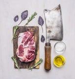在一个切板的新鲜,可口未加工的猪肉牛排有肉的,油,在木土气背景的盐草本屠刀的 免版税库存图片