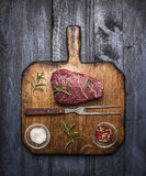 在一个切板的未加工的ribeye牛排有一把叉子的,与迷迭香盐和胡椒在土气木背景,顶视图 免版税库存照片