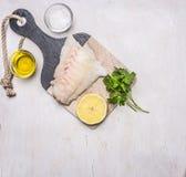 在一个切板的生鱼内圆角有柠檬、草本、黄油和盐边界的,地方文本木土气背景顶视图 库存图片