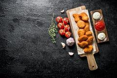 在一个切板的鸡块用不同的调味汁、大蒜和蕃茄 免版税库存照片