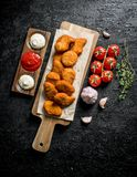 在一个切板的鸡块用不同的调味汁、大蒜和蕃茄 免版税库存图片