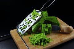在一个切板的绿色pesto乳酪有乳酪磨丝器的 库存图片