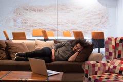 在一个创造性的办公室供以人员睡觉在一个沙发 免版税库存照片