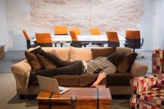 在一个创造性的办公室供以人员睡觉在一个沙发 免版税库存图片
