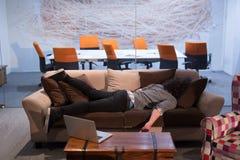 在一个创造性的办公室供以人员睡觉在一个沙发 图库摄影