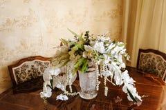 在一个别致的水晶花瓶的新娘花束在一个被雕刻的被上漆的木桌特写镜头 库存照片
