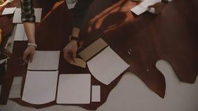 在一个制造的车间的工匠顶视图把被切开的曲线放在一块皮革在桌上的上 股票视频