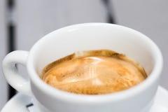 在一个加奶咖啡杯子的新鲜,温暖的咖啡在户外一张浅灰色的桌上 免版税库存图片
