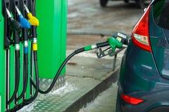 在一个加油站的汽车换装燃料在冬天关闭 免版税图库摄影