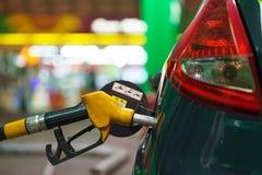 在一个加油站的汽车换装燃料在冬天在晚上 图库摄影