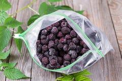 在一个包裹的冷冻莓果在木背景 库存图片