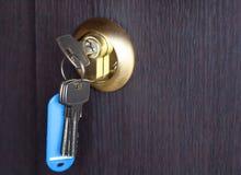 在一个匙孔的一把新的钥匙在一个木门 免版税库存照片