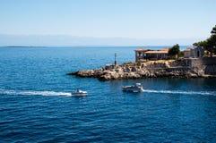 在一个半岛的灯塔与两条小船 免版税图库摄影