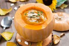 在一个南瓜的菜奶油色汤在一张木桌上 免版税库存照片