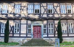 在一个历史的半木料半灰泥的房子的红色门在戈斯拉尔 免版税库存图片