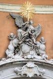 在一个历史建筑的墙壁上的金黄巴洛克式的雕象在贬小儿的 库存照片