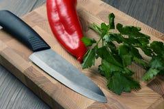 在一个厨房板的陶瓷刀子用胡椒和草本 免版税库存照片