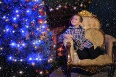 在一个发光的蓝色圣诞树和壁炉旁边的男孩 库存图片