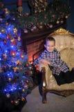 在一个发光的蓝色圣诞树和壁炉旁边的男孩 免版税图库摄影