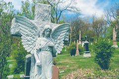 在一个发怒雕象前的天使在公墓 图库摄影