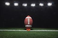 在一个发球区域的橄榄球在光下的晚上 库存图片