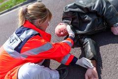 在一个受伤的骑自行车的人的德国医务人员检查血压 库存图片