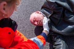 在一个受伤的骑自行车的人的德国医务人员检查血压 库存照片