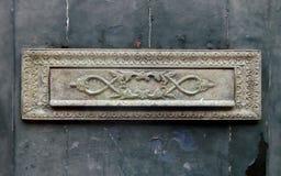在一个古老威尼斯式门的老黄铜邮件存取口 库存照片