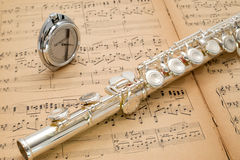 在一个古老音乐比分的银色长笛和口袋节拍器 免版税库存照片