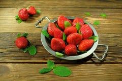 在一个古色古香的盘子的大红色草莓在老木板说谎 库存照片