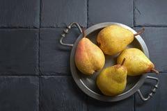 在一个古色古香的盘子的成熟梨,在一块黑板岩石头-在右边 在左边-黑背景 免版税库存照片