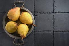 在一个古色古香的盘子的成熟梨,在一块黑板岩石头-在左边 在右边-黑背景 免版税库存图片