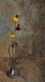 在一个古色古香的银色花瓶的野花有板岩背景 免版税库存照片
