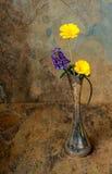 在一个古色古香的银色花瓶的紫色和黄色野花在sla 库存照片