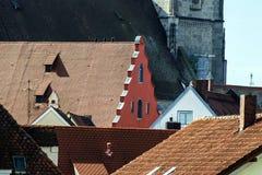 在一个古镇的原始的房子的屋顶的之间红色盾 免版税库存图片