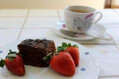 在一个可口和鲜美巧克力蛋糕和一杯咖啡的三个新鲜的红色草莓在背景的附近 图库摄影