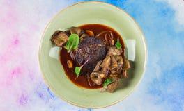 在一个可口调味汁的开胃牛排用蘑菇 免版税图库摄影