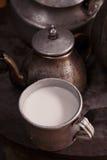 在一个吉尔吉斯yurt厨房里挤奶杯子和老茶壶和水壶 免版税库存图片