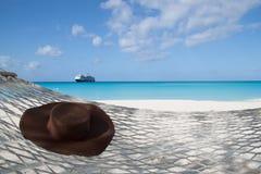 在一个吊床的帽子在海滩 免版税库存图片
