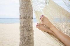 在一个吊床的美好的女性脚在海滩 免版税库存照片