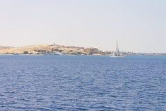 在一个含沙海岛前面的一条游艇 库存照片