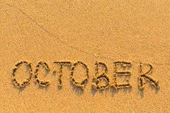 在一个含沙海海滩-用手得出的10月 免版税库存照片