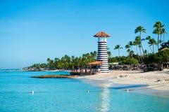 在一个含沙热带海岛上的灯塔有棕榈树的 免版税库存照片