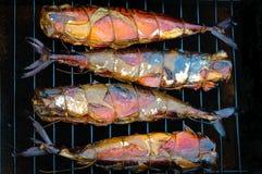 在一个吸烟者格栅的熏制的鱼在黑背景 免版税库存图片