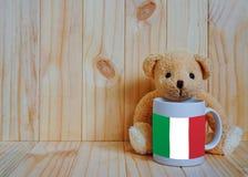 在一个咖啡杯的意大利旗子有玩具熊和木背景的 免版税库存图片